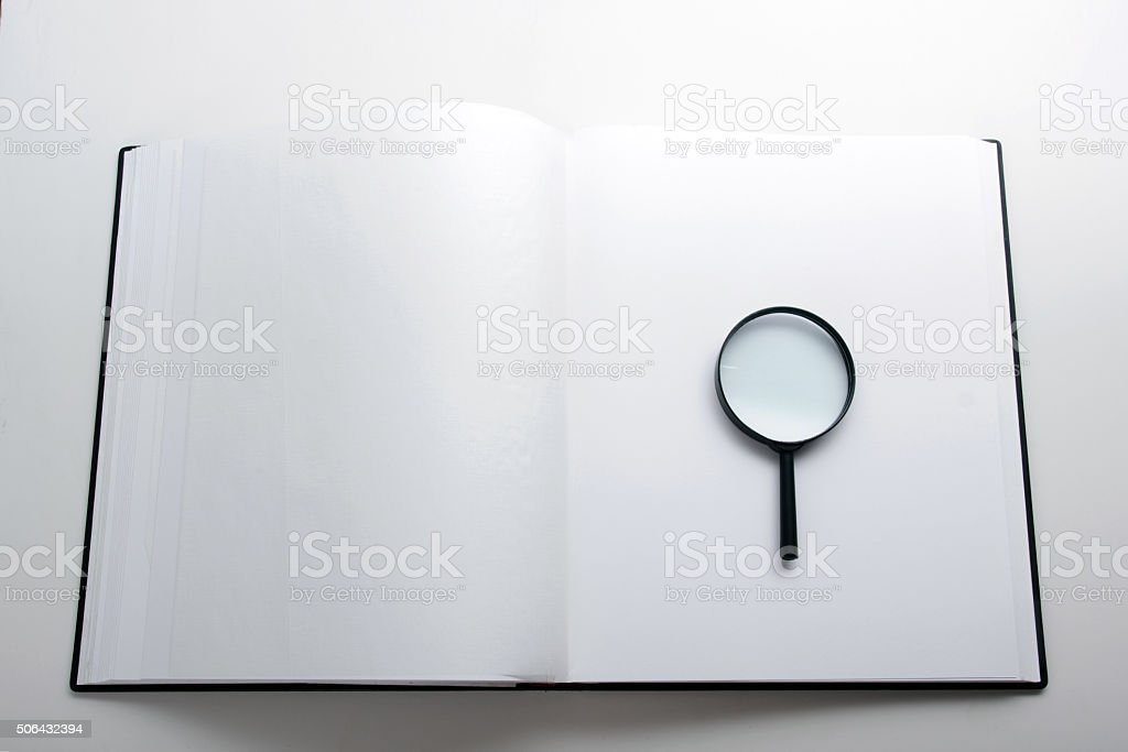 Open book, hardback books with magnifying glass stock photo