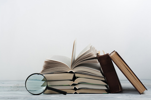 istock Open book, hardback colorful books on wooden table. Magnifier. Back to school. Copy space for text. Education business concept 690053584