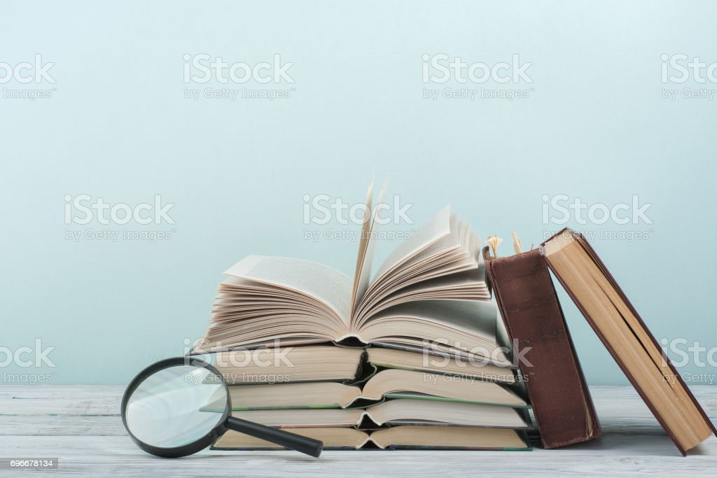 Open book, hardback colorful books on wooden table. Magnifier. Back to school. Copy space for text. Education business concept stock photo