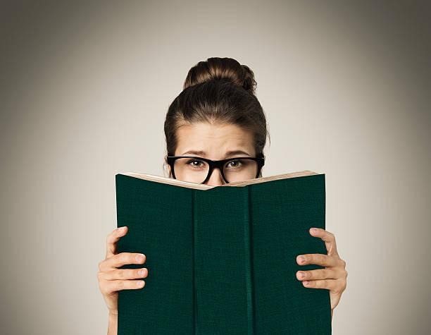 Livro aberto se escondendo o rosto, mulher olhos leitura em óculos, Gray - foto de acervo