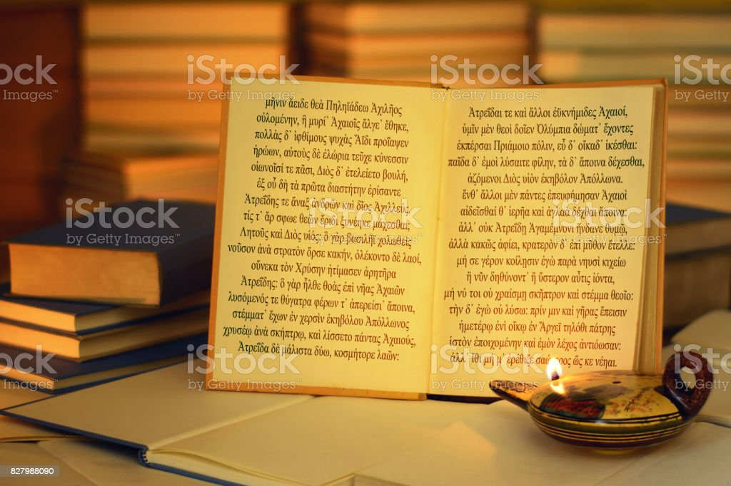 Open book illuminated by an oil lamp. Iliad opening lines. stock photo