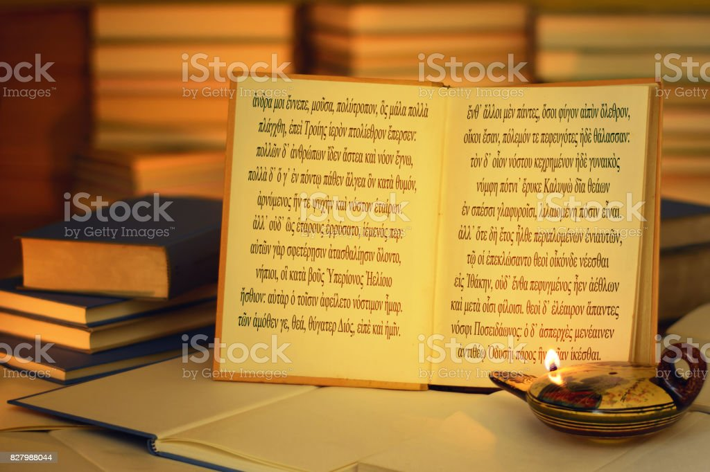 Open book illuminated by an oil lamp. Odyssey opening lines. stock photo