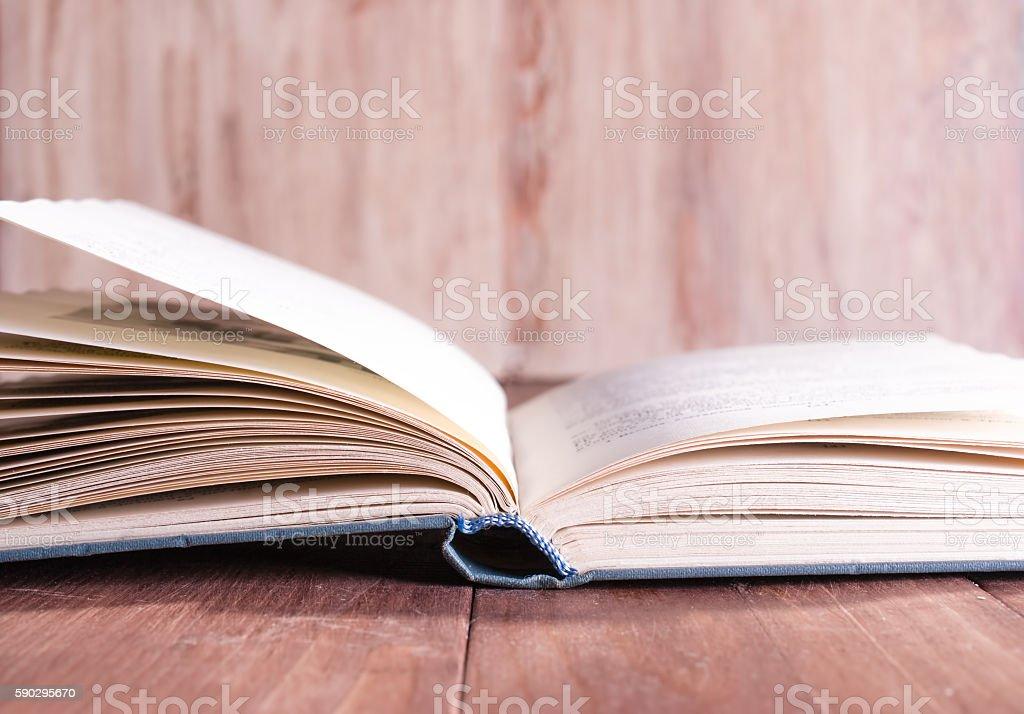Open book lying on a wooden table royaltyfri bildbanksbilder