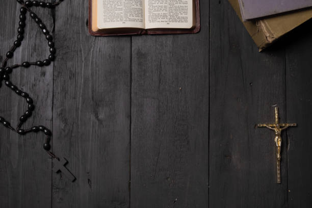 Open book of Bible and crucifix on dark table, top view Flat lay image of New Testament, cross and rosary on old black background catholicism stock pictures, royalty-free photos & images