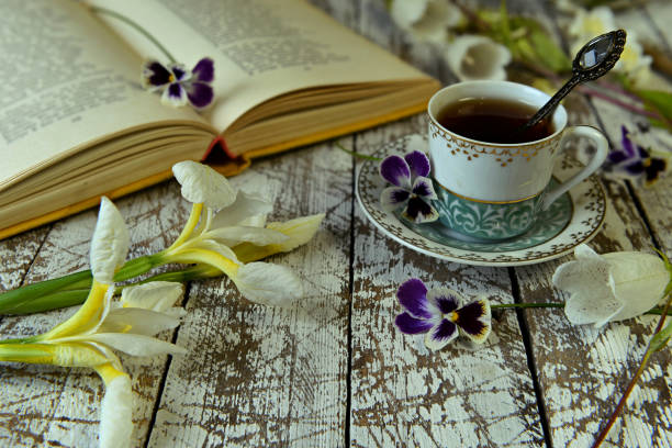 Open book of poetry, old cup of tea and flowers on table. stock photo