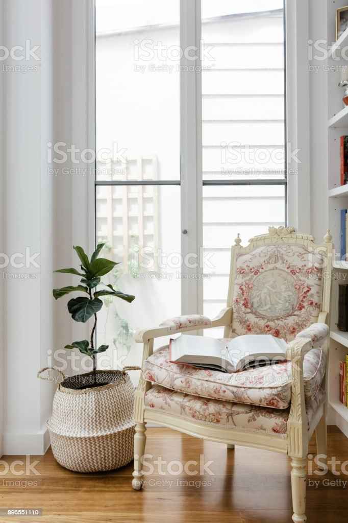 Open book on a comfotable vintage reading chair in a renovated home stock photo