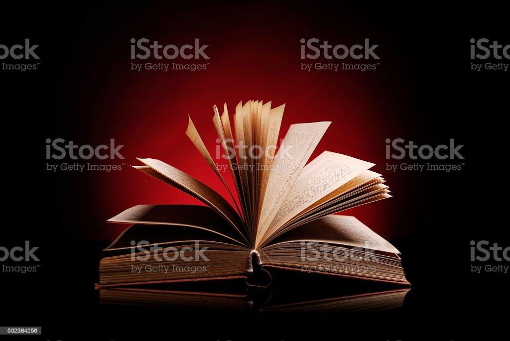 Abrir libro sobre un fondo rojo oscuro - foto de stock