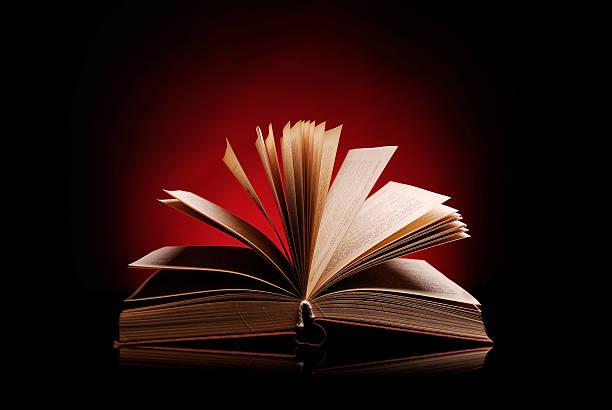 Offenes Buch auf einem dunkelroten Hintergrund – Foto
