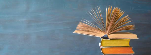 Offenes Buch über einen Haufen Bücher, Panorama, Leseerziehung, Literatur, guter Kopierplatz – Foto