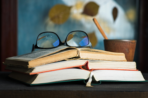 Open book on a table with autumn abstract background on the window