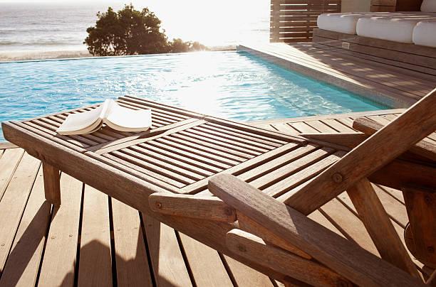 offenes buch auf lounge-sessel am pool - sun chair stock-fotos und bilder