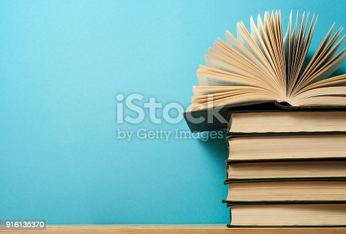 1018285596 istock photo Open book on stack of books on wooden table. Education background. Back to school. Free copy space. 916135370