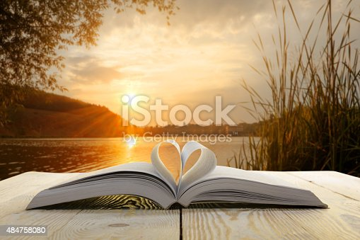 istock Open book on wooden table on natural blurred background. 484758080