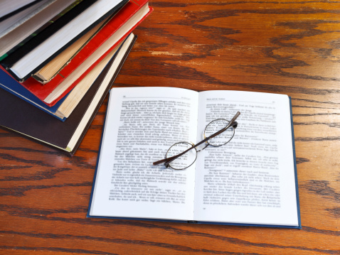 above view of blank open book and glasses on wooden table