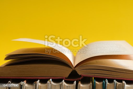 Open book on yellow background, hardback books on wooden table. Education and learning background. Back to school, studying. Copy space for text