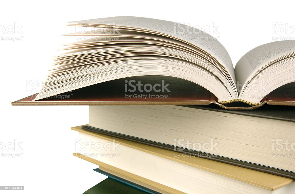 Open book over a pile of closed books in white background stock photo