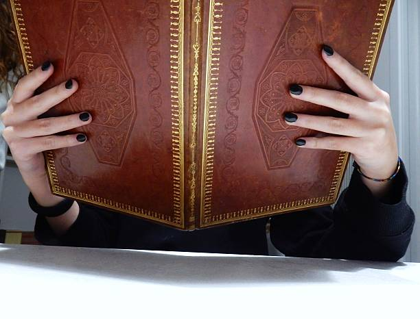 Libro aperto Benevento, Campania, Italy - February 8, 2016: the hands of a young girl holding up an old book libro stock pictures, royalty-free photos & images