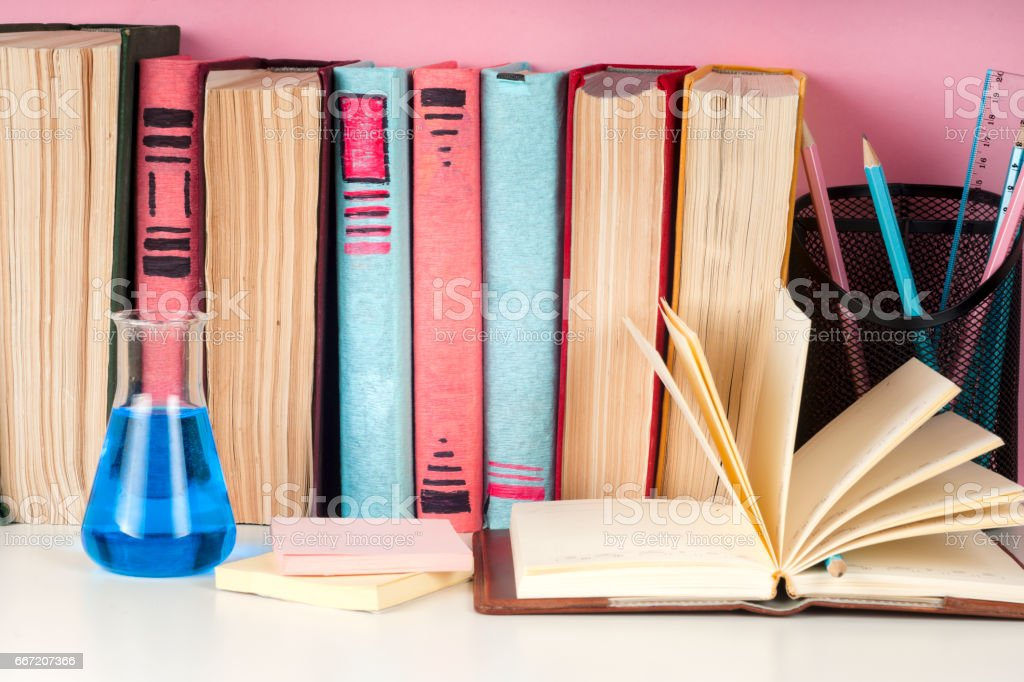 Open book, stack of colorful hardback books on light table. Back to school. Copy space for text royalty-free stock photo