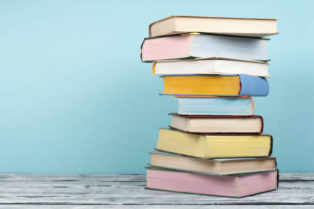Open book, stacking, hardback books on wooden table and background. Back to school. Copy space for text stock photo