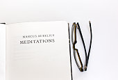 Open Book, Title Page: Marcus Aurelius Meditations. White background. Reading glasses rest on the white background, with copy space available.