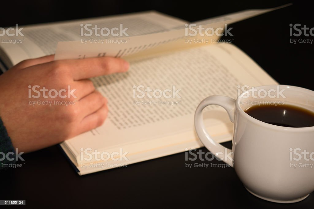 open book with a cup of coffee on wood table stock photo