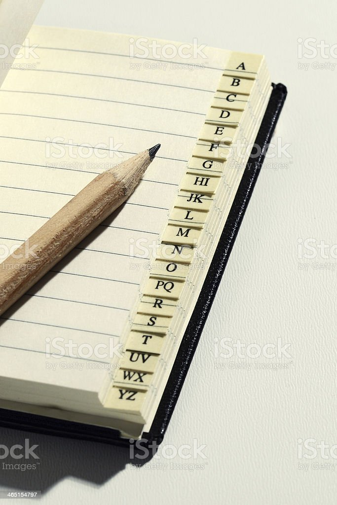 Open book with alphabet tabs and pencil royalty-free stock photo