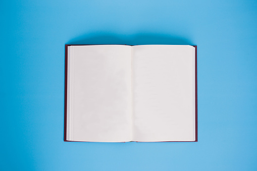 Open book with blank paper pages over bright blue background - with copy space