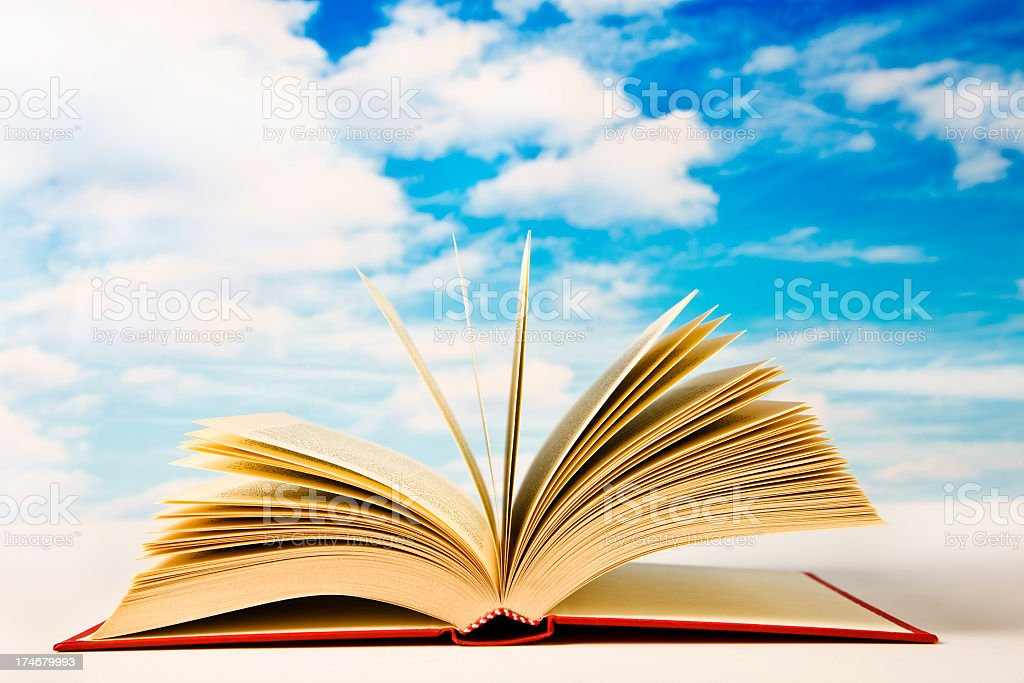 Open book with blue sky and cloud in background stock photo