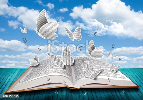 istock Open book with butterflies letters on blue sky 450953735