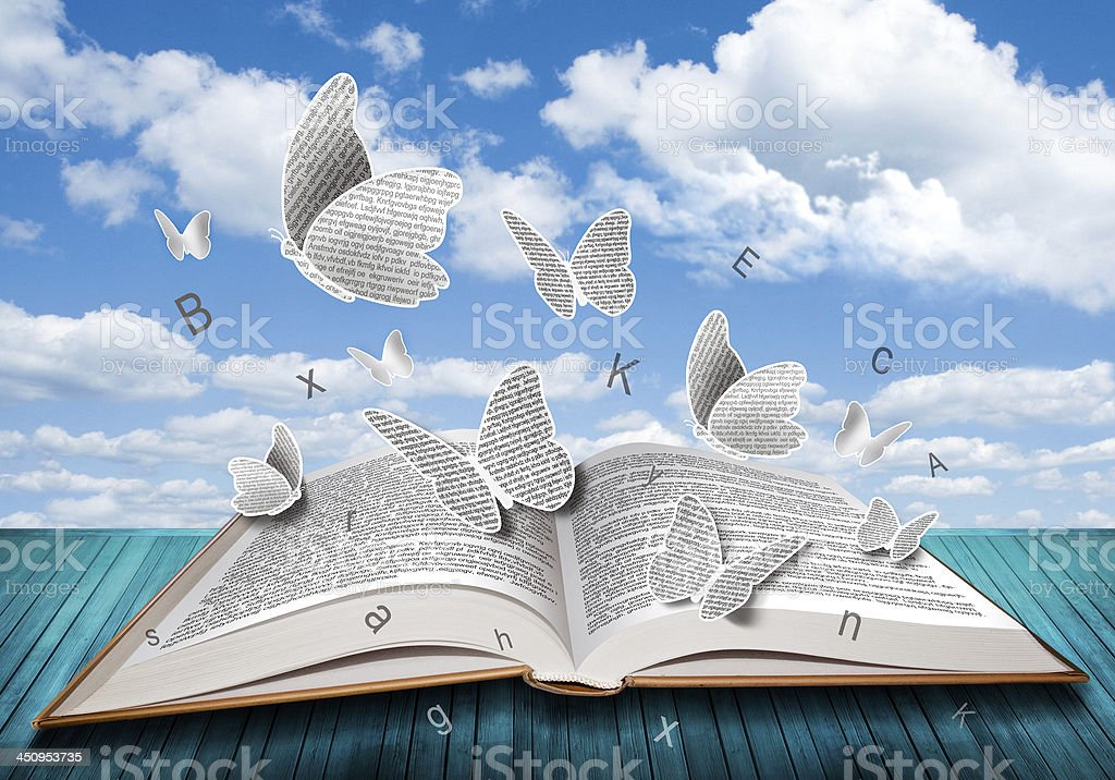 Open book with butterflies letters on blue sky stock photo