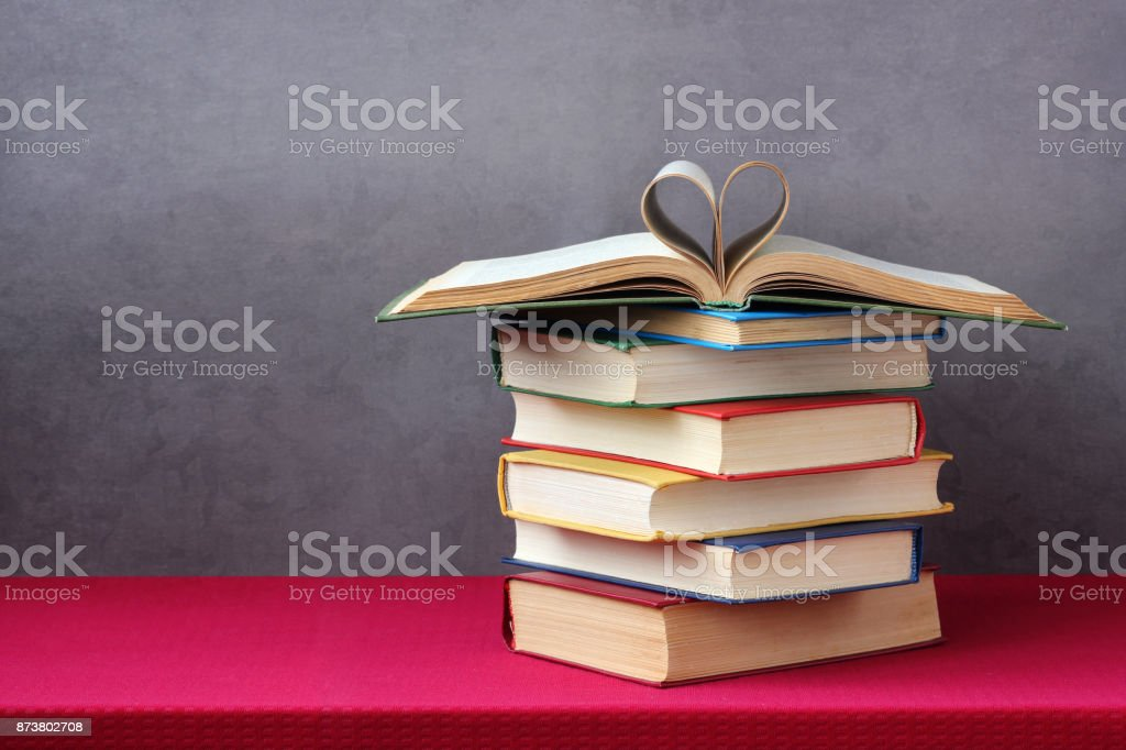 Open book with curled leaves in the shape of a heart. stock photo