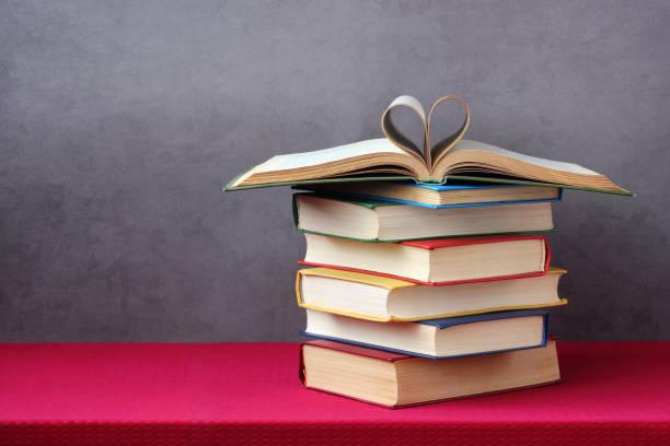 Livro aberto com folhas enroladas em forma de um coração. - foto de acervo