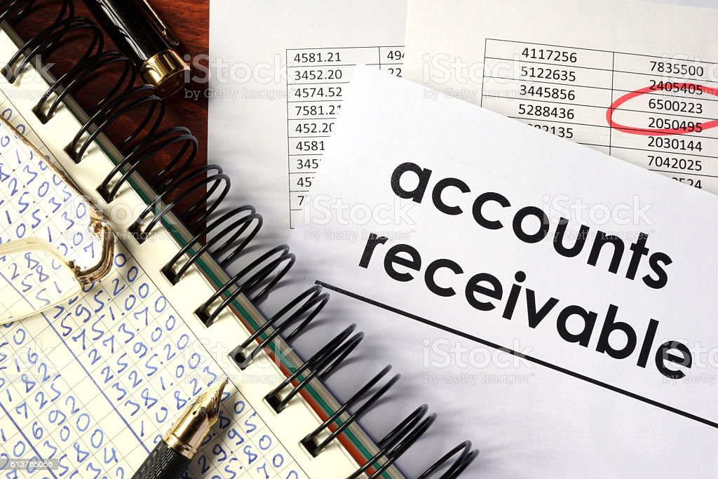 Open book with figures and paper with words  accounts receivable. stock photo