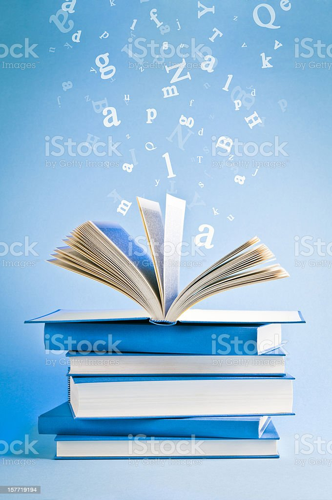 Open book with flying, scattered letters isolated on blue background royalty-free stock photo