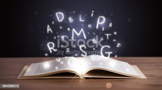 istock Open book with glowing letters flying out 934095510