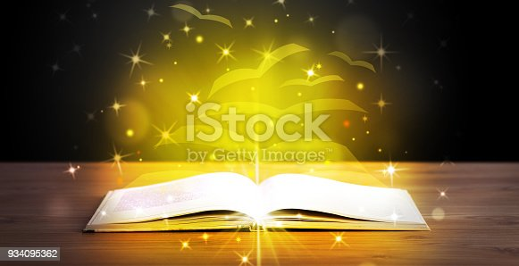 istock Open book with golden glow flying paper pages 934095362
