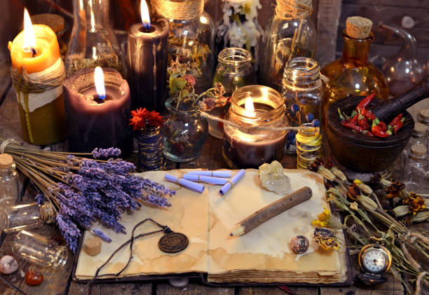Open book with healing herbs, lavender flowers, candles, potion bottles and magic objects stock photo