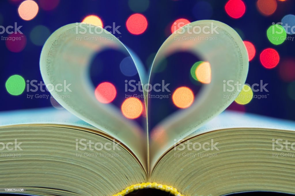 Open book with heart shape from paper pages on table in soft night...