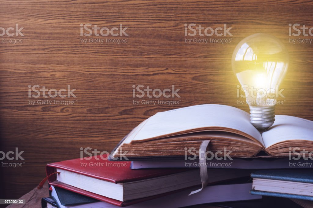 Open book with light bulb and hardback books on wood wall background. Free space for text. Selective focus stock photo