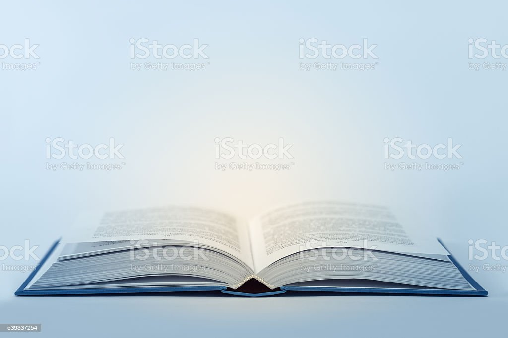 Open book with light inside stock photo