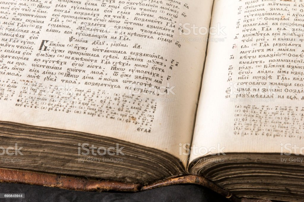 Open book with light spotlight on text. Reading of opened book educate reader. Ancient Bible text reading on black background. Russian bible royalty-free stock photo