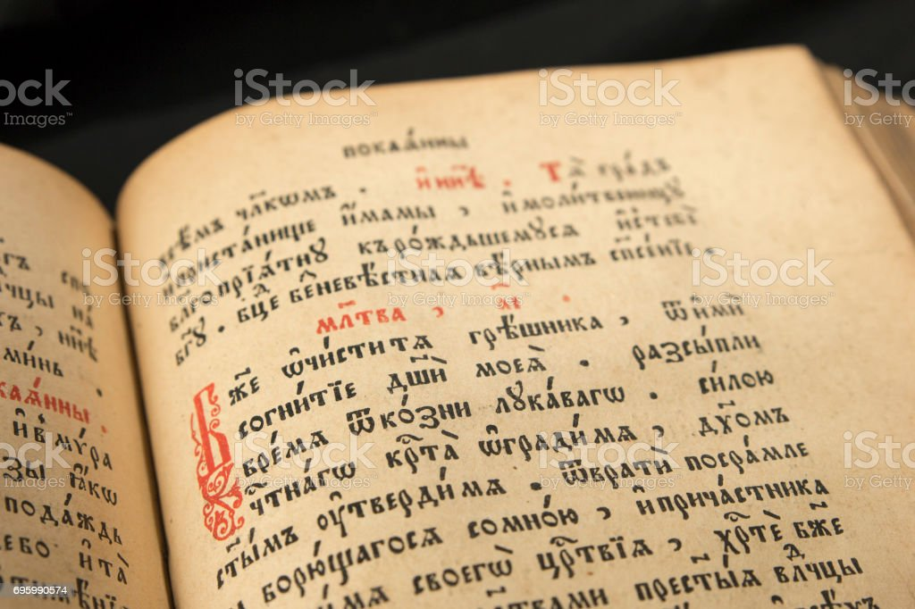 Open book with light spotlight on text. Reading of opened book educate reader. Ancient Bible text reading on black background. Russian bible. Red initial letter in slavonic text. stock photo
