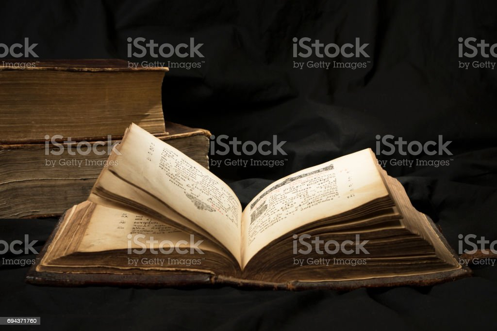 Open book with light spotlight on text with books on background. Ancient book collection. Reading of opened book educate reader. Ancient Bible text reading on black background. Russian bible royalty-free stock photo