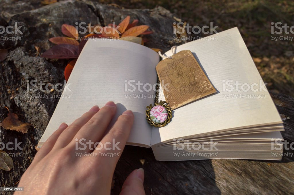 open book with vintage bookmark and womans hand stock photo