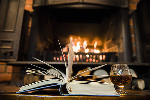 open book with whisky in front of a fireplace - grillbuch stock-fotos und bilder