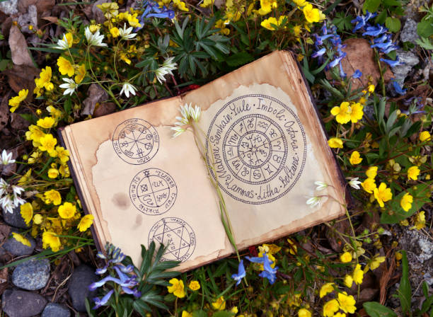Open book with wiccan festivals chart among spring flowers. stock photo