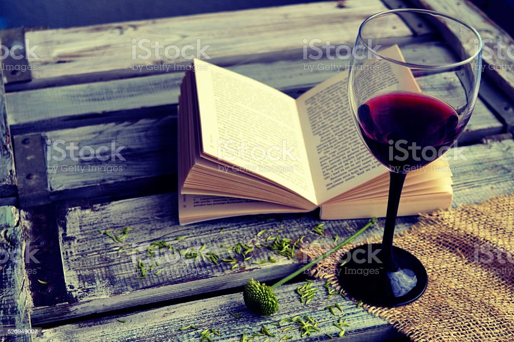 Open book with wine glass on a wooden background stock photo