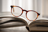Open books and glasses over bokeh background