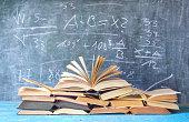 open books in front of a blackboard