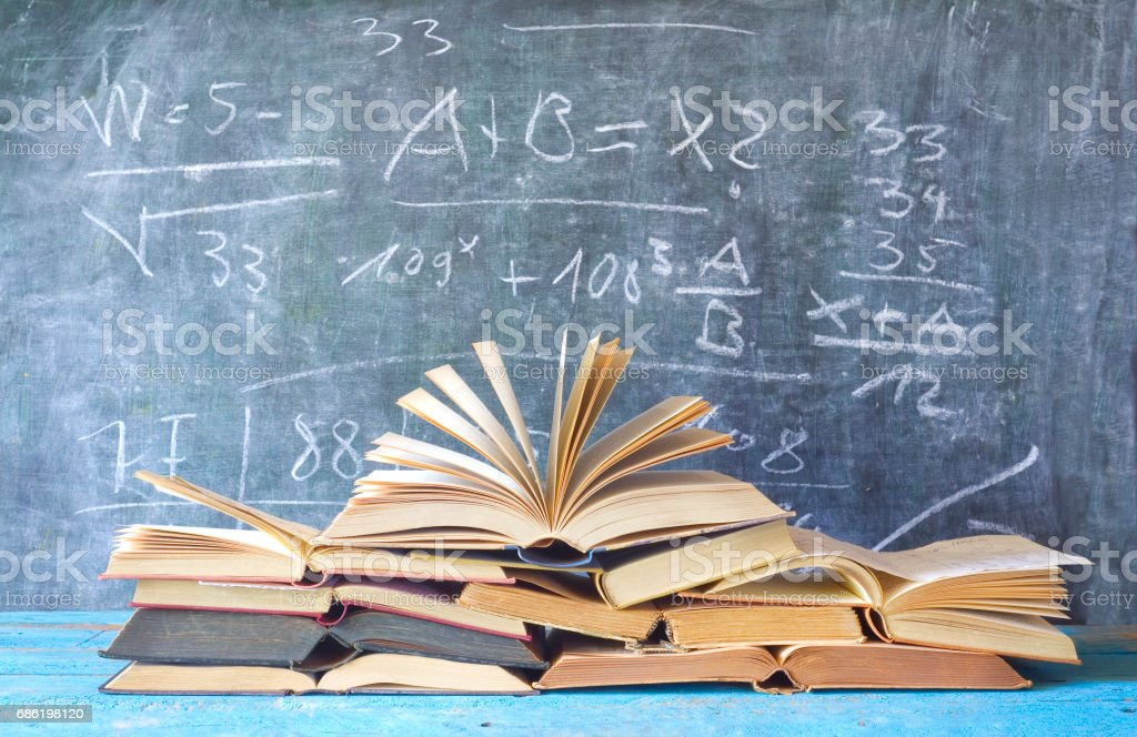 open books in front of a blackboard stock photo